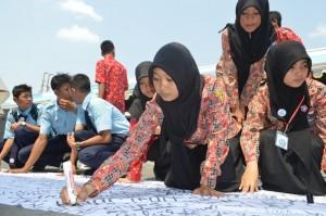 Para pelajar ketika menorehkan tanda tangan sebagai bentuk penolakan penggunaan narkoba. (Foto: Zaenal Huda)