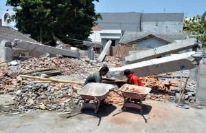 Sejumlah pekerja tengah membersihkan puing-puing tiang gedung laboratorium MAN II yang telah dirobohkan lantaran diduga menyalahi UU Cagar Budaya. (Foto: Zaenal Huda)